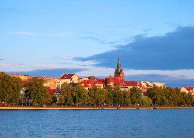Glimpse of the downtown and lakeshore lit by the sunset rays over Elckie lake in Elk, Poland