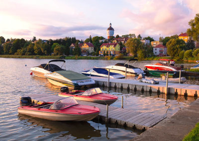 Small boat marina at the Ełckie lake with a historic water tower in Elk, Poland
